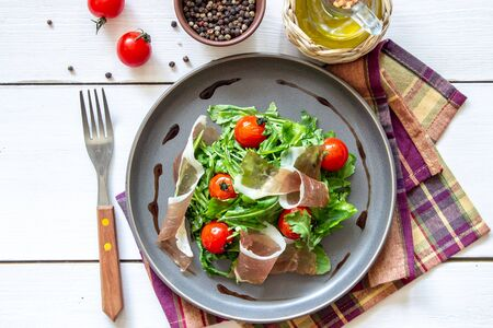Salad with arugula, tomatoes and prosciutto. Italian cuisine. Healthy eating. Diet Foto de archivo