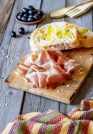 Prosciutto ham and bread on a wooden background. Italian cuisine. Village style Stock Photo