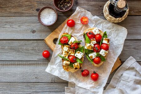 Bruschettas with tomatoes and cheese. Italian cuisine. Simple style. Vegetarian food Reklamní fotografie