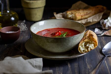 Spanish tomato soup gazpacho on a wooden background. Dark food photography. Zdjęcie Seryjne
