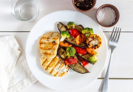 Grilled chicken with grilled vegetables on a wooden background. Healthy eating. Diet. Recipes. Broccoli, eggplant, carrot, pepper.