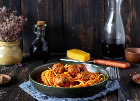 Pasta with meatballs and tomato sauce on a wooden background. Recipes. Italian cuisine. Rustic. Homemade food