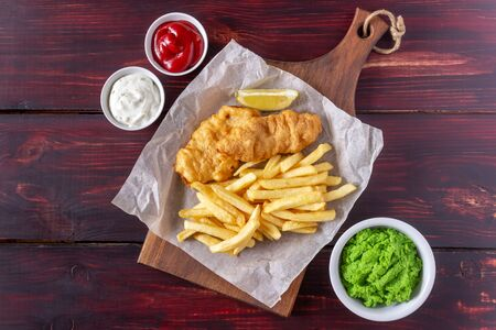 Fish and chips on a wooden background. British fast food. Recipes. Snack to beer. Traditional british food.