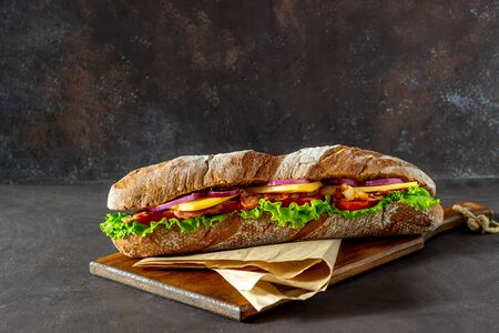 A sandwich of dark bread with salad, bacon, tomatoes, cheese and onions. Baguette. Breakfast. Fast food. Healthy eating. Recipes.