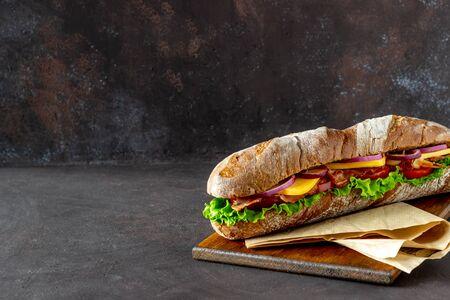 Ein Sandwich aus dunklem Brot mit Salat, Speck, Tomaten, Käse und Zwiebeln. Stangenbrot. Frühstück. Fast Food. Gesundes Essen. Rezepte. Standard-Bild