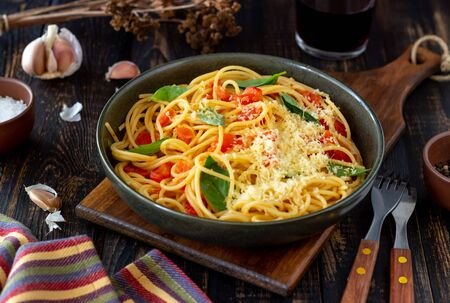 Pasta spaghetti with tomatoes, basil and parmesan cheese. Italian cuisine. Recipe. Vegetarian food. Healthy eating Standard-Bild