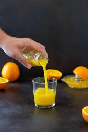 Freshly squeezed orange juice on a dark background. Healthy eating. Diet. Vegetarian food