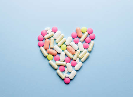 The heart is laid out of pills on a blue background. Health. Medicine. Pharmacy.