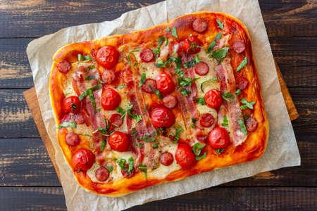Pizza with bacon, sausage, mozzarella, tomatoes and basil. Italian cuisine. Recipe. 免版税图像