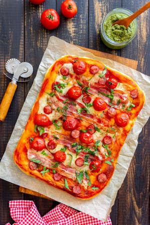 Pizza with bacon, sausage, mozzarella, tomatoes and basil. Italian cuisine. Recipe.