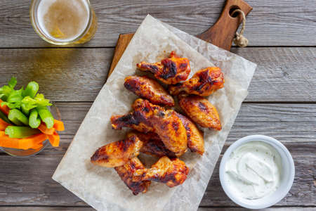 Barbecue chicken wings with carrots, celery and white sauce. Grill. Recipe.