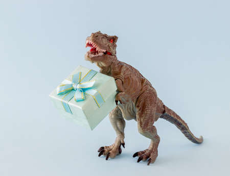 Dinosaur holds a gift box. Minimal concept. Idea.