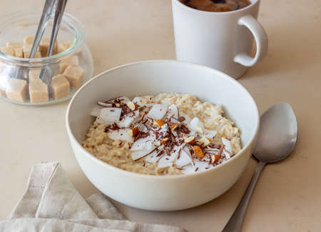 Oatmeal porridge with almonds, coconut and chocolate. Healthy eating. Vegetarian food. Breakfast. Diet.