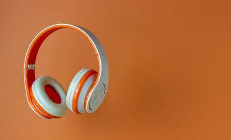 Orange headphones on a orange background. Minimal concept. Mock-up. Music. Levitation. 免版税图像
