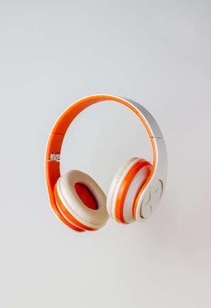 Orange headphones on a white background. Minimal concept. Mock-up. Music. Levitation.