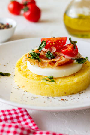 Polenta with mozzarella, bacon and tomatoes. Italian cuisine. Recipe. 免版税图像