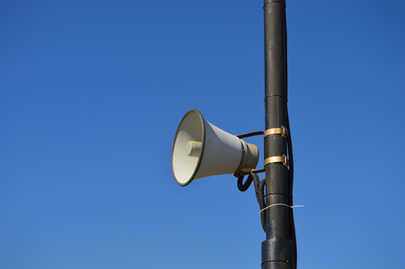 Loudspeaker on a pole against a clear blue sky in the daylight