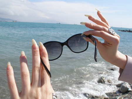 Woman hands with long finger nails with sunglasses sea view