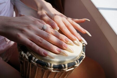 Female Hands with Long Fingernails on a djembe drum Imagens
