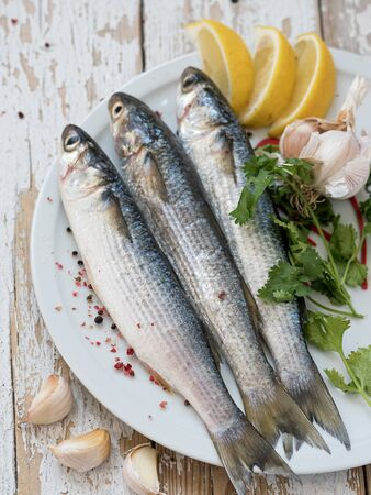 Fresh mullet is on a white plate. Sea fish. Spices, pepper, lemon. Located on a white wooden vintage background. View from above.