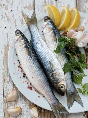 Le mulet frais est sur une plaque blanche. Poisson de mer. Épices, poivre, citron. Situé sur un fond vintage en bois blanc. Vue d'en-haut.