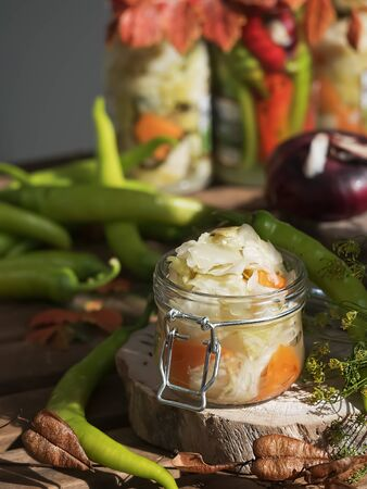Canned and fermented food in glass jars. Cucumbers and carrots, green chilli peppers on a brown wooden background. Fermented food. Autumn canning. Conservation of a farm crop. Natural food, close-up. Autumn