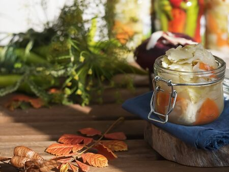 Jar with fermented vegetables. Cabbage, dill, carrots in the foreground on a blue linen napkin. Fermented, canned vegetarian food concept. The concept of canned food. Close-up. Homemade healthy food. Reklamní fotografie