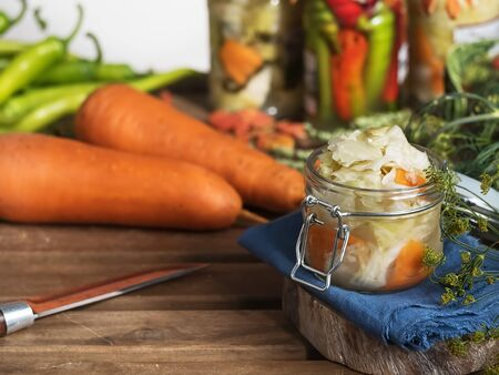 Jar with fermented vegetables. Cabbage, dill, carrots in the foreground on a blue linen napkin, near a carrot. Fermented, canned vegetarian food concept. The concept of canned food. Close-up. Homemade healthy food. Reklamní fotografie