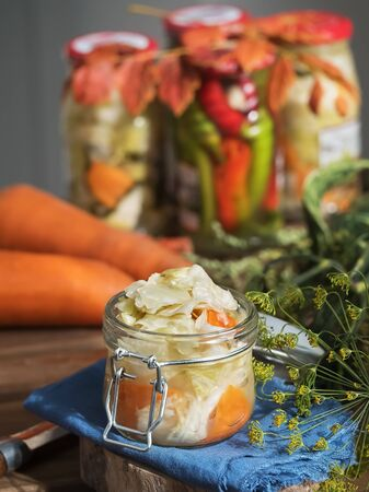 Jar with fermented vegetables. Cabbage, dill, carrots in the foreground on a blue linen napkin, near a carrot. Fermented, canned vegetarian food concept. The concept of canned food. Close-up. Homemade healthy food. 版權商用圖片