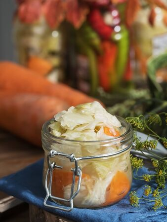 Jar with fermented vegetables. Cabbage, dill, carrots in the foreground on a blue linen napkin, near a carrot. Fermented, canned vegetarian food concept. The concept of canned food. Close-up. Homemade healthy food. Stockfoto