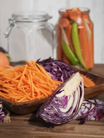 Sliced carrots and red cabbage on a wooden dish. Harvesting products. Kitchen, homemade food. Fermented, canned vegetarian food. Jars of fermented food. The concept of canned food. Close-up. Autumn. Vertical frame.