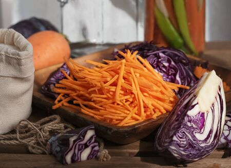 Sliced carrots and red cabbage on a wooden dish. Harvesting products. Kitchen, homemade food. Fermented, canned vegetarian food. Jars of fermented food. The concept of canned food. Close-up. Autumn. Horizontal frame. Reklamní fotografie