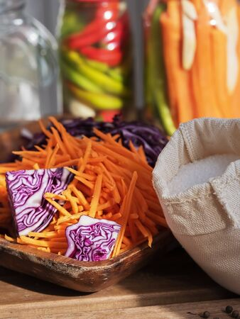 Sliced carrots and red cabbage on a wooden dish. Harvesting products. Linen bag with salt. Kitchen, homemade food. Fermented, canned vegetarian food. Jars of fermented food. The concept of canned food. Close-up. Autumn. Horizontal frame.