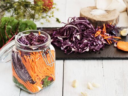 Fermentation of the crop for the winter. Carrots, dill, cabbage, garlic, salt, chard. Natural, environmentally friendly products. Jar with chopped vegetables for fermentation. Close-up. Autumn.