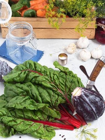 A close-up of chard leaves of a red cabbage. The knife cuts the cabbage. Harvesting for the fermentation of vegetables. Fresh farm vegetables in a wooden box. The concept of healthy organic food. Stok Fotoğraf