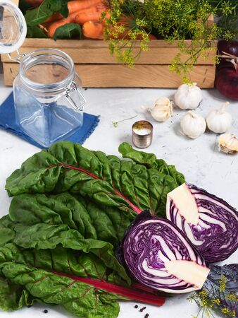 A close-up of chard leaves with halved red cabbage. Harvesting for the fermentation of vegetables. Fresh farm vegetables in a wooden box. The concept of healthy organic food. Stok Fotoğraf