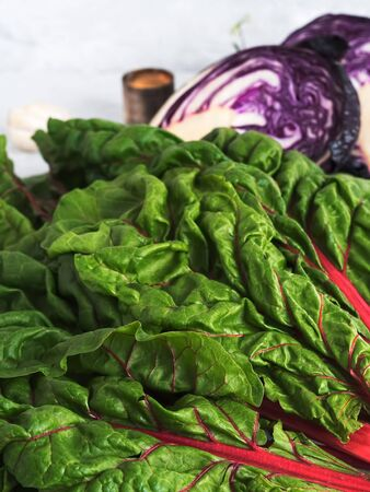 Close-up of chard leaves with half-sliced red cabbage. Harvesting for the fermentation of vegetables. Fresh farm vegetables in a wooden box. The concept of healthy organic food. Stok Fotoğraf
