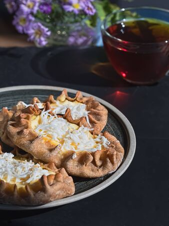 Karelian Pirakka pies located on a gray plate on a black stone background. Near a cup of tea. Traditional dish of Karelia and Finland from rye flour with different fillings. Close-up
