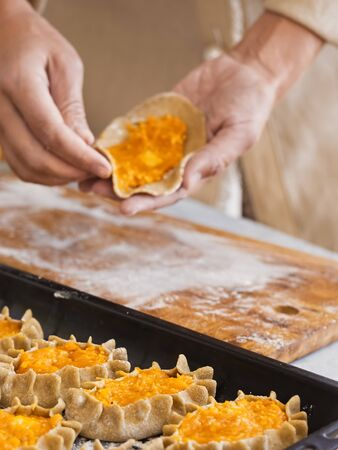 Stage of preparation of Karelian pies. Pies are located on a baking sheet, ready for baking. In the background, a woman is preparing pies. Dish of national cuisine - piirakka. Close-up. Banco de Imagens