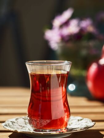 Tea in a glass of armudu on a saucer, located on a wooden table in the loggia. In the background are flowers and ripe pomegranate. Bright sunny day. Close-up.