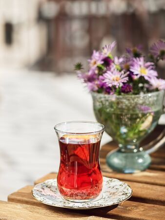 Tea in a glass of armudu on a saucer, located on a wooden table in the loggia. In the background are flowers . Bright sunny day. Close-up.