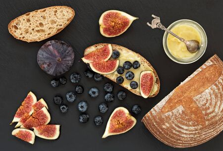 Fresh homemade bread, homemade baking. Blank for sandwich, figs, blueberries, sauce. Top view. Black stone background. 写真素材 - 133473153