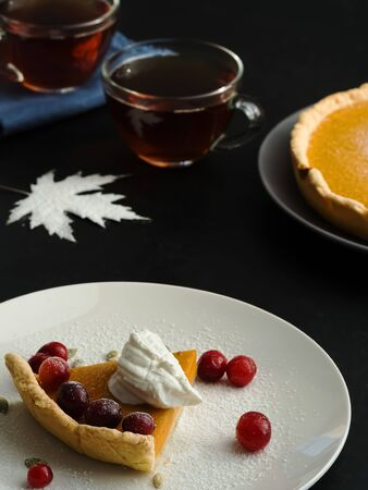 A slice of homemade traditional American pumpkin pie decorated with cream and cranberries is located on a white plate. Close-up. On a black background multi-colored autumn leaves and a cups with tea.