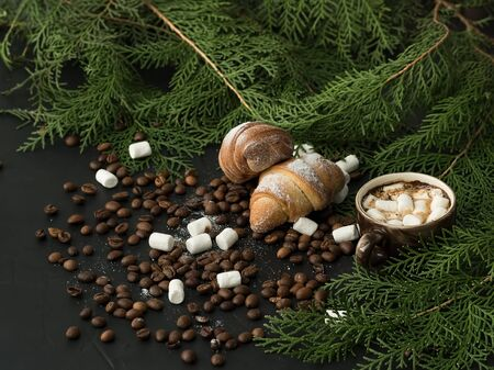 Cup of coffee with marshmallows on the background of coniferous branches. Marshmallows and roasted coffee beans laid out on a black background. There are two croissants on the grains. Close-up