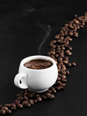 White cup with fragrant espresso on a black background, steam rises above the cup. Roasted coffee beans are located around a cup of coffee and in the background. Close-up.