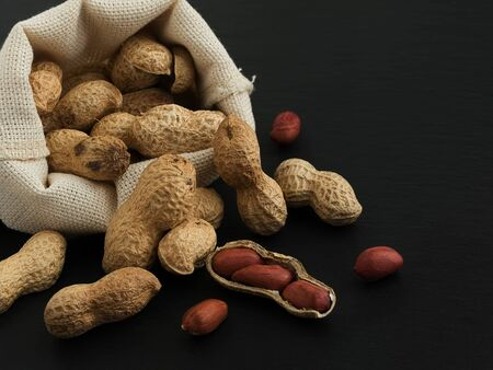 Peanuts in a linen bag on a black stone background, close-up. Peanuts are scattered on the background. Peeled peanuts and peanuts in a peel. Super food. Copy space 免版税图像
