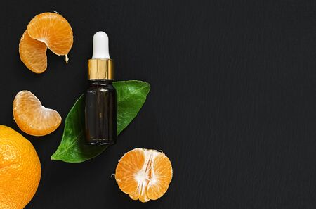 Mandarin essential oil (citrus) in a glass bottle on a leaf of tangerine tree. Black stone background. Next to a bottle of oil are mandarin slices. Flat lay. Copy space.