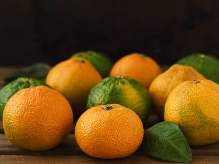 Fresh, ripe tangerines on a wooden table. The basis for the preparation of essential oils. Close-up. Stock fotó