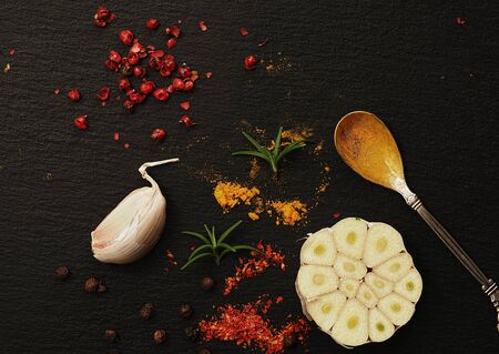 Top view of oriental spices on a black stone background. Spices in and around vintage teaspoons on a black table. Cut across the head of garlic. Flat lay.