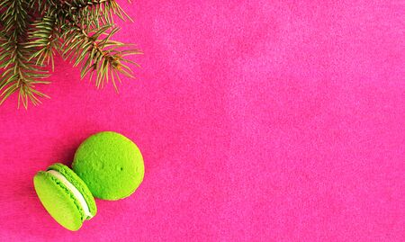 Two green macaroon with fondant on a red paper background. Near the branch of the Christmas tree. Flat lay, copy space for text. Postcard or banner concept.